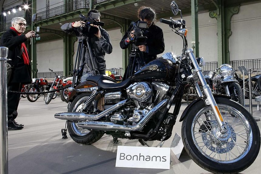 Cameramen shoot the 1,585 cc Harley Davidson Dyna Super Glide, donated to Pope Francis last year and signed by him on its tank, which is displayed as part of Bonham's Les Grandes Marques du Monde vintage and classic cars sale at the Grand Palais in P