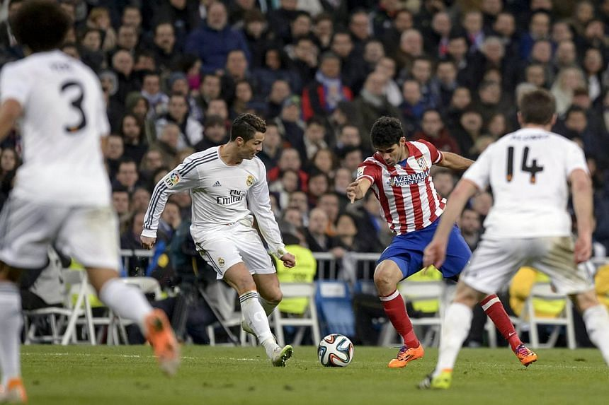 Real Madrid's Portuguese forward Cristiano Ronaldo (left) vies with Atletico Madrid's Brazilian forward Diego da Silva Costa during the Spanish Copa del Rey (King's Cup) semi-final first-leg football match at the Santiago Bernabeu stadium in Madrid o