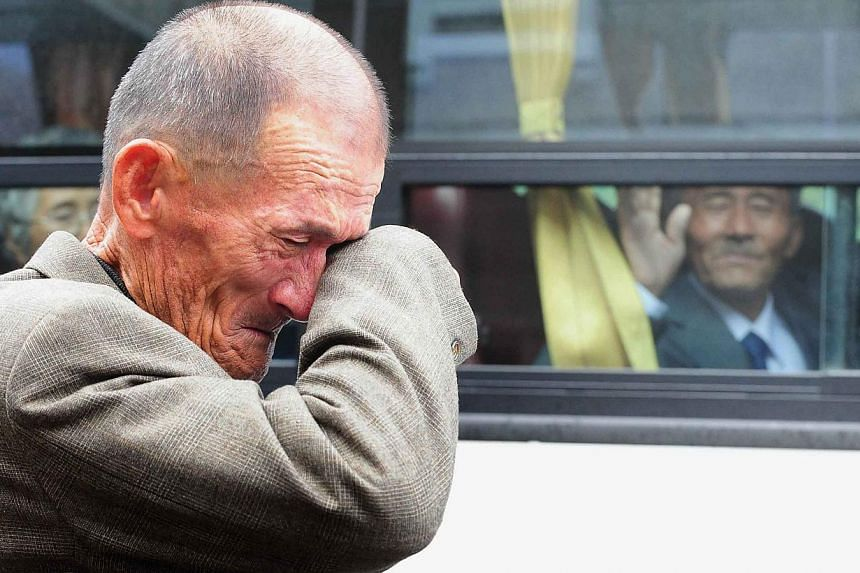 An elderly South Korean man wiping his tears as a North Korean relative (in the bus) waves to say good-bye after a luncheon during a separated family reunion meeting at the Mount Kumgang resort on the North's south-eastern coast, near the border on O