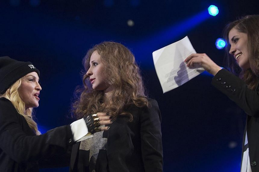 Madonna (left) introduces Russian punk rock band Pussy Riot members Nadezhda Tolokonnikova (right) and Maria Alyokhina during the Amnesty International benefit concert in the Brooklyn borough of New York, on Feb 5, 2014.-- PHOTO: REUTERS