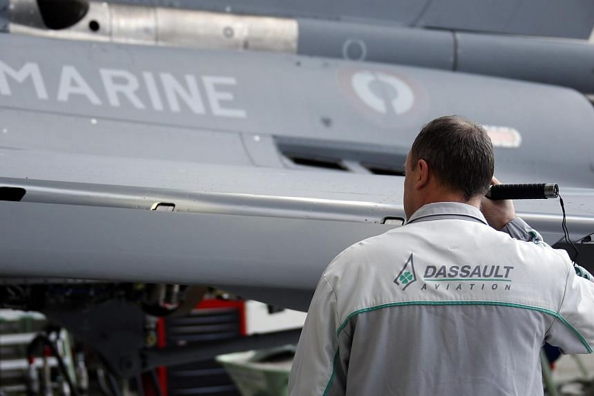 A worker checks a Rafale jet fighter as he works on the assembly line in the factory of French aircraft manufacturer Dassault Aviation in Merignac near Bordeaux, southwestern France, on Jan 10, 2014. India's defence minister on Thursday ruled ou