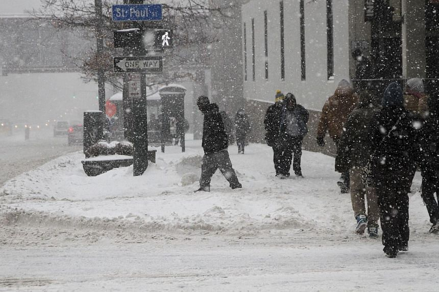 Pedestrians walk on Main Street during a snow storm on Feb 5, 2014 in Rochester, New York.Treacherous snow and freezing rain struck the north-eastern United States (US) on Wednesday, disrupting thousands of flights and causing traffic chaos for