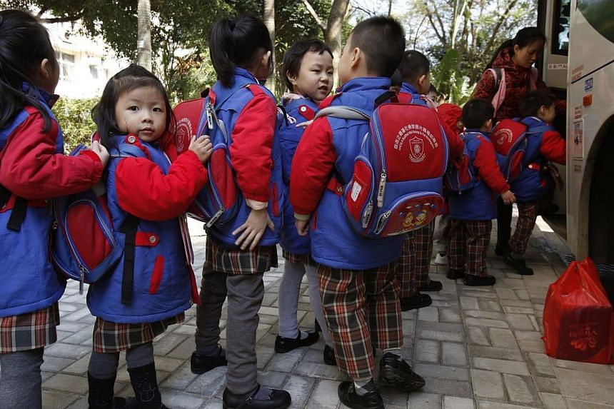 Students, who live in Shenzhen, line up for a school bus after school in Hong Kong on Dec 19, 2013, before crossing the border back to mainland China. One recent winter dawn, more than 100 parents from the mainland started lining up outside a pr