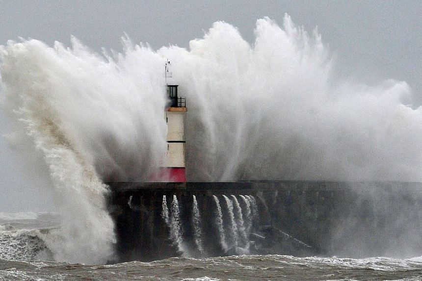 Newhaven Lighthouse is battered by waves during stormy weather in Newhaven on the southern coast of England on Feb 5, 2014. -- PHOTO: AFP/GLYN KIRK