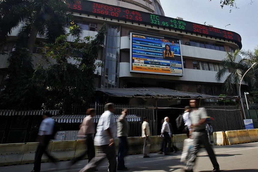 People walk past the Bombay Stock Exchange (BSE) building in Mumbai on Feb 6, 2014. India on Friday is likely to cut its estimate of 5 per cent growth forecast for the fiscal year that ends on March 31, thanks to a slower-than-expected recovery