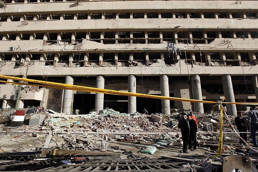 Police officers inspect the site of a bomb attack in front of the damaged Cairo Security Directorate building, which includes police and state security, in downtown Cairo on Jan 24, 2014.-- FILE PHOTO: REUTERS