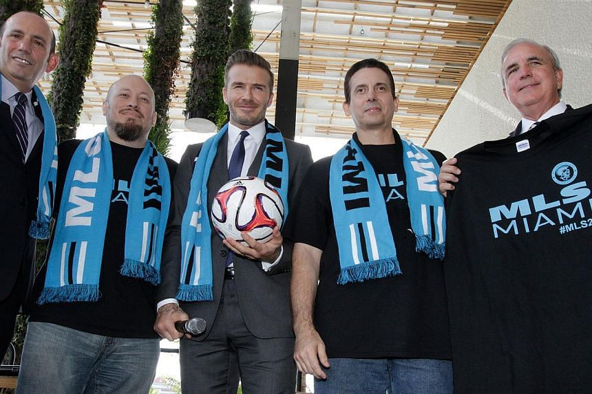 Former England and Manchester United star, David Beckham (centre) poses for photos after holding a press conference at the Perez Art Museum Miami, in Miami, Florida, on Feb 5, 2014. Beckham's new team in Miami will not take to the pitch until at