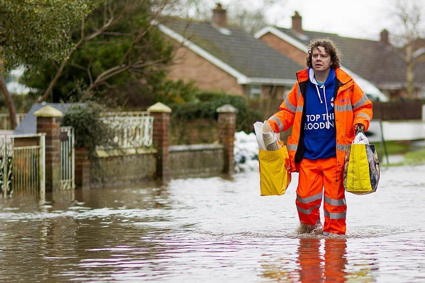 A man walks through flooded streets in the village of Moorland in Somerset, south-west England, on Feb 6, 2014. Britain deployed Royal Marines on Thursday to help with devastating floods after what officials said was likely the worst spell of wi