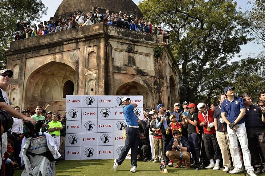 World Number one golfer Tiger Woods of the US (centre) plays a round of golf at the Delhi Golf Club in New Delhi in this handout released by World Sports Group (WSG) on Feb 4, 2014.Woods made it official on Thursday, confirming on his website t