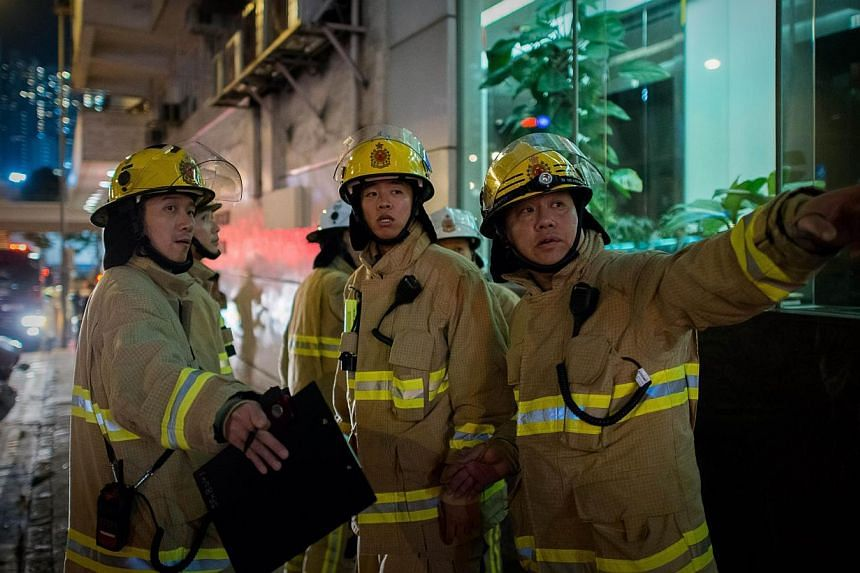 Firemen are seen near the site where a World War II-era bomb weighing almost a tonne was discovered in Hong Kong on Feb 6, 2014.Hong Kong police on Friday successfully dismantled the largest World War II bomb yet found in the city after its dis