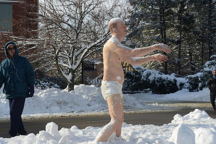 """A man looks at a sculpture entitled """"Sleepwalker"""" on the campus of Wellesley College, on February 6, 2014 in Wellesley, Massachusetts. The sculpture is part of an exhibit by artist Tony Matelli, and has prompted an online student petition to have it"""