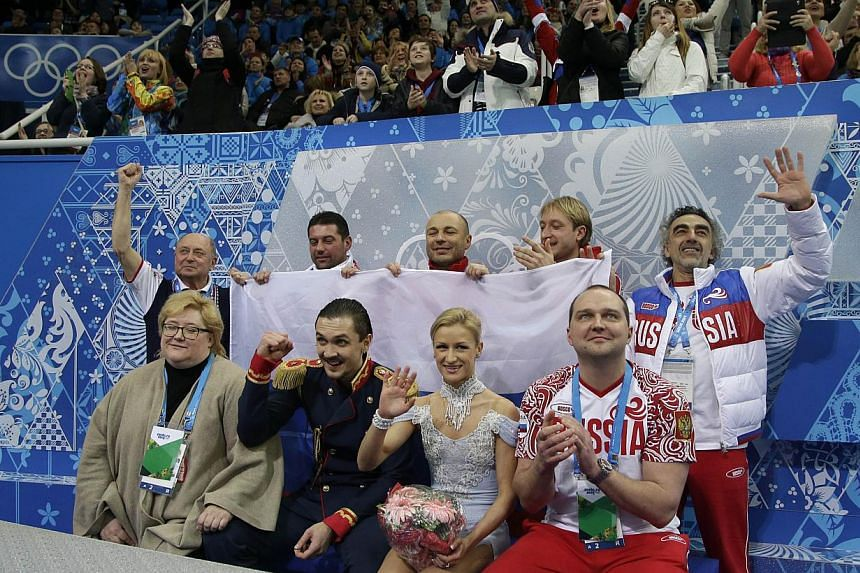 Russia's Maxim Trankov (2nd left) and Russia's Tatiana Volosozhar (center) celebrate with teammate Russia's Yevgeny Plushenko (top, 2nd right) after performing the Figure Skating Pairs Team Short Program at the Iceberg Skating Palace during the Sochi