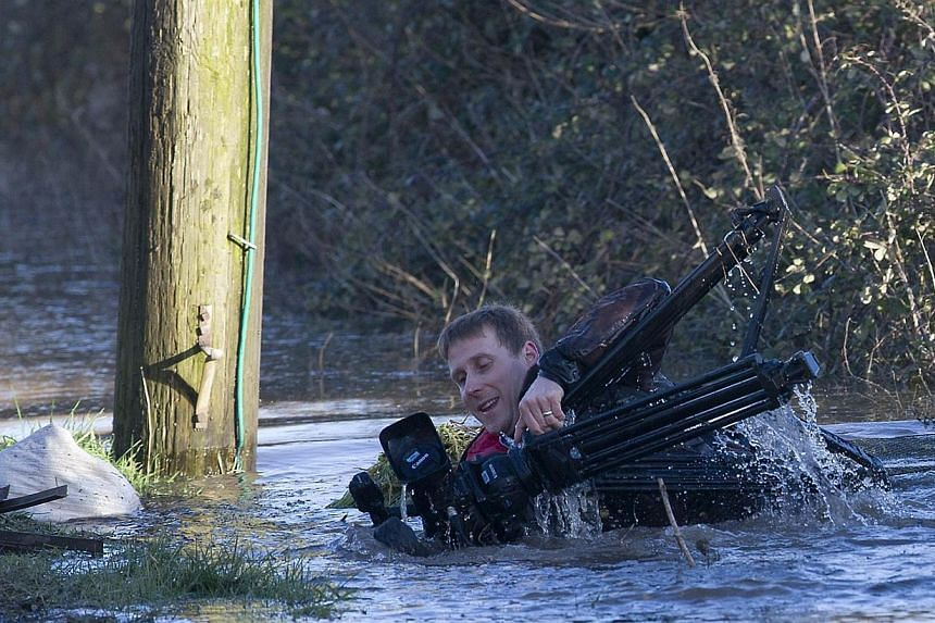 A television cameraman falls into deep flood waters while filming during flood relief operations in Moorland, some 19km north-east of Taunton, on Feb 7, 2014. -- PHOTO: AFP