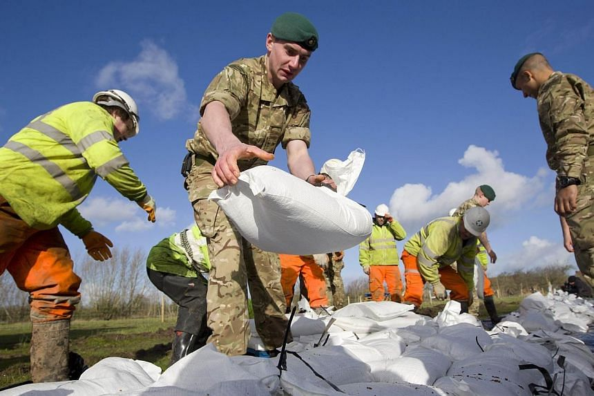 British Royal Marines help lay sandbags during flood relief operations in Moorland on Feb 7, 2014. -- PHOTO: AFP