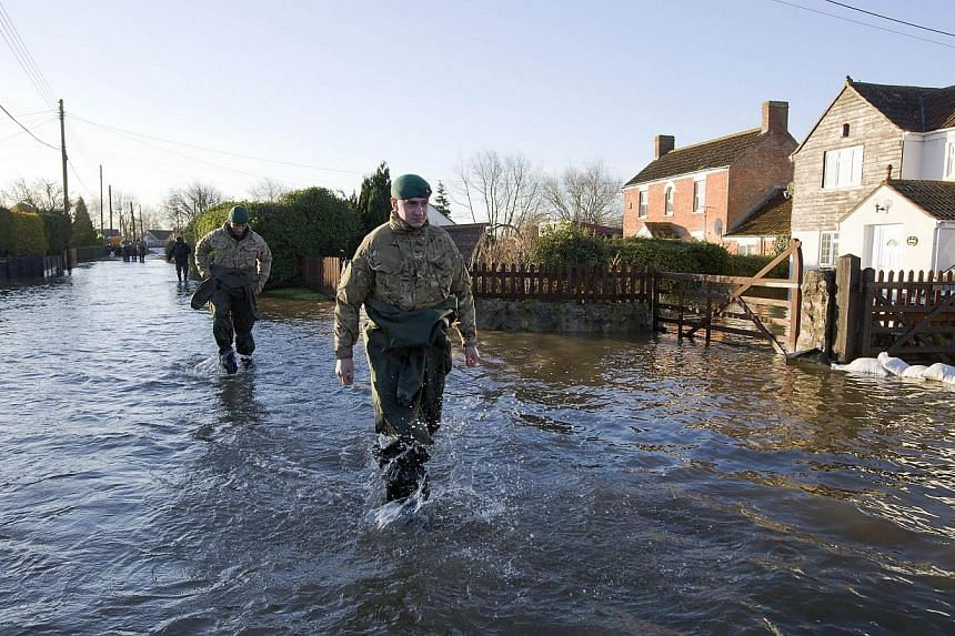 British Royal Marines wade through flood waters on a street in Moorland as they take part in flood relief operations. -- PHOTO: AFP