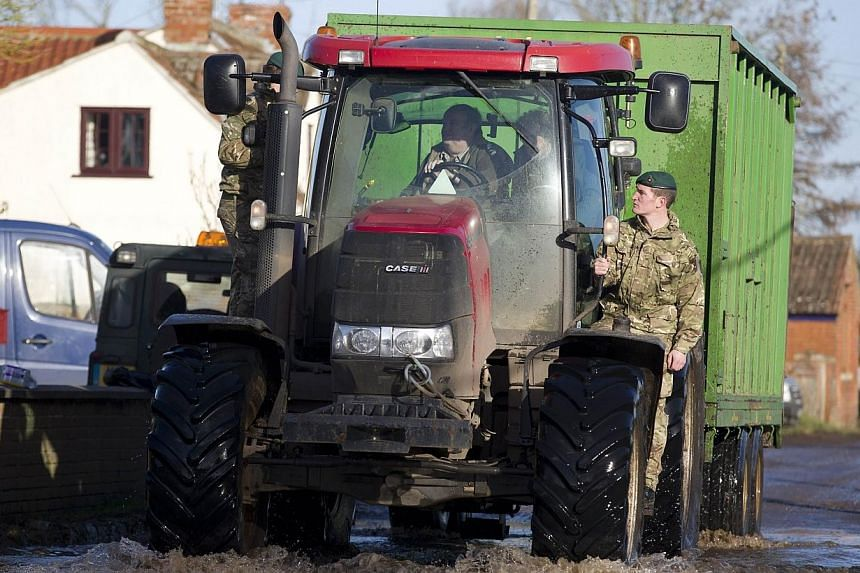 British Royal Marines hitch a ride on a tractor during flood relief operations in Moorland on Feb 7, 2014. -- PHOTO: AFP