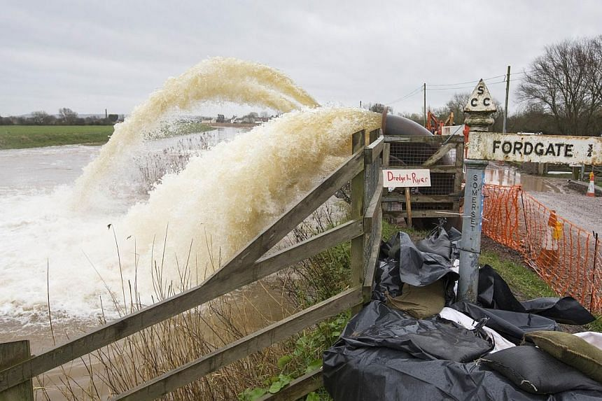 """Flood water is pumped from fields into the River Parrett at Northmoor Green in Somerset, south-west England, on Feb 6, 2014, by a sign that reads """"Dredge the river"""". -- PHOTO: AFP"""