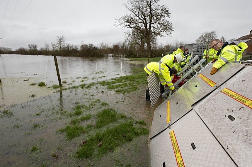 Environment Agency workers build flood defences around properties in Moorland in Somerset, south-west England, on Feb 6, 2014. -- PHOTO: AFP