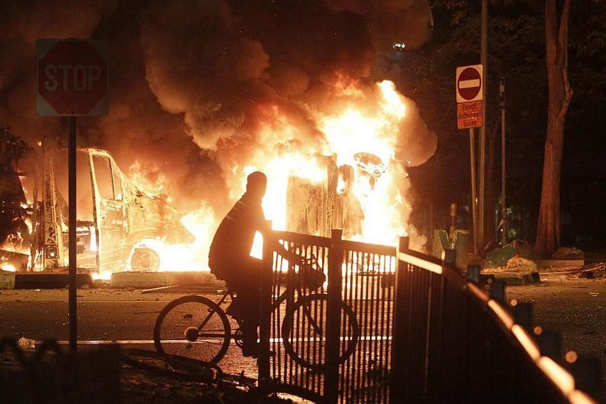 A man cycles pass a burning ambulance and police car during the Little India riot on Dec 8, 2013.Indian national Chinnappa Vijayaragunatha Poopathi on Friday became the first among 25 men accused of taking part in the Little India riot last Dec