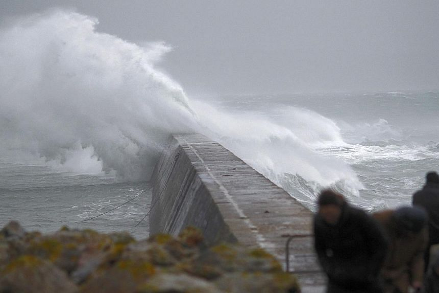 Waves crash over the breakwater of Saint Evette harbour at Esquibien in Brittany as an Atlantic storm hits western France, Dec 23, 2013. A storm cut electricity to some 55,000 homes in north and northwest France, power distributor ERDF said on F