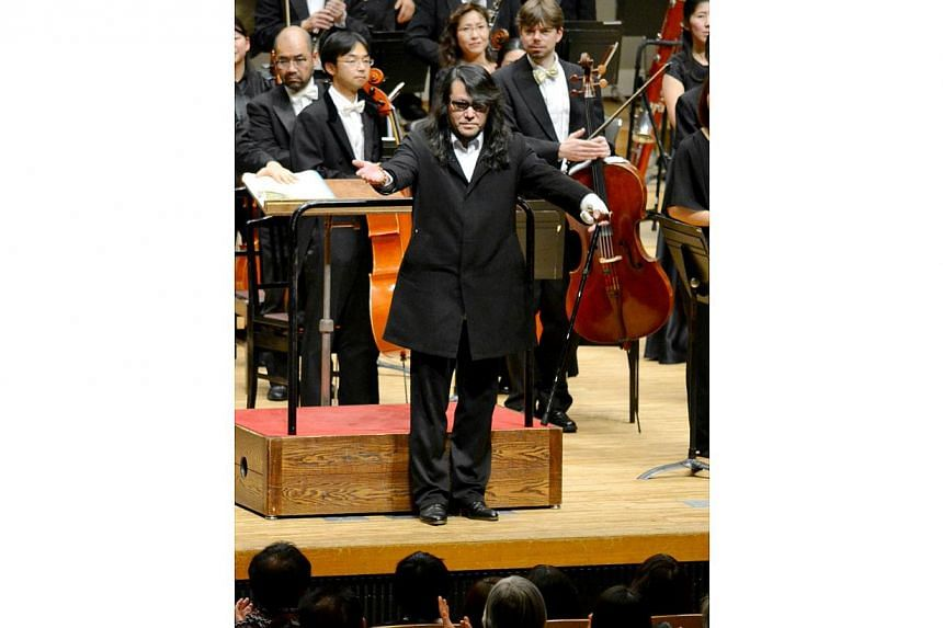 "This picture taken on December 28, 2013 shows Mamoru Samuragochi dubbed ""Japan's Beethoven"" reacting to the audience after his symphony No.1 was performed at a concert hall in Hiroshima, western Japan. The musical brains behind a supposedly deaf comp"