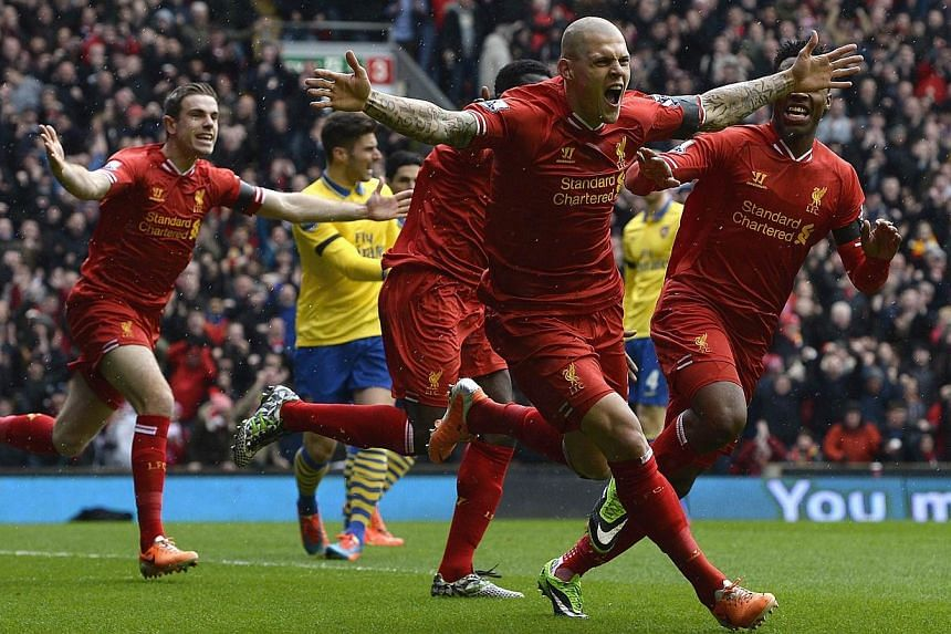 Liverpool's Martin Skrtel (centre) celebrates scoring against Arsenal during their English Premier League match at Anfield on Saturday, Feb 8, 2014.Liverpool re-energised their title challenge with a magnificent 5-1 rout of sorry leaders Arsena