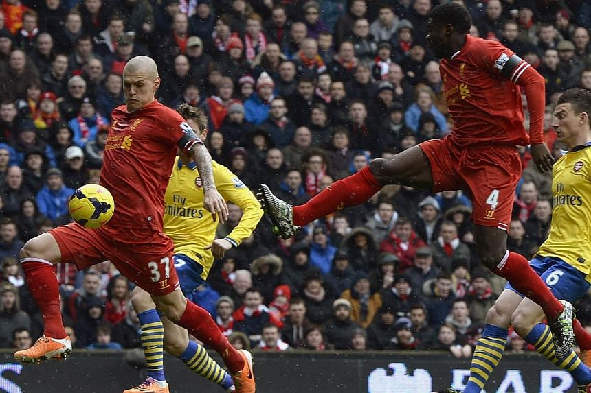 Liverpool's Martin Skrtel (left) shoots to score against Arsenal during their English Premier League match at Anfield on Saturday, Feb 8, 2014. -- PHOTO: REUTERS