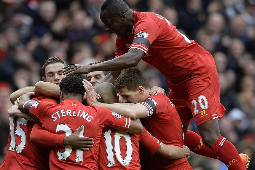 Liverpool players celebrate after scoring against Arsenal during their English Premier League match at Anfield on Saturday, Feb 8, 2014. -- PHOTO: REUTERS