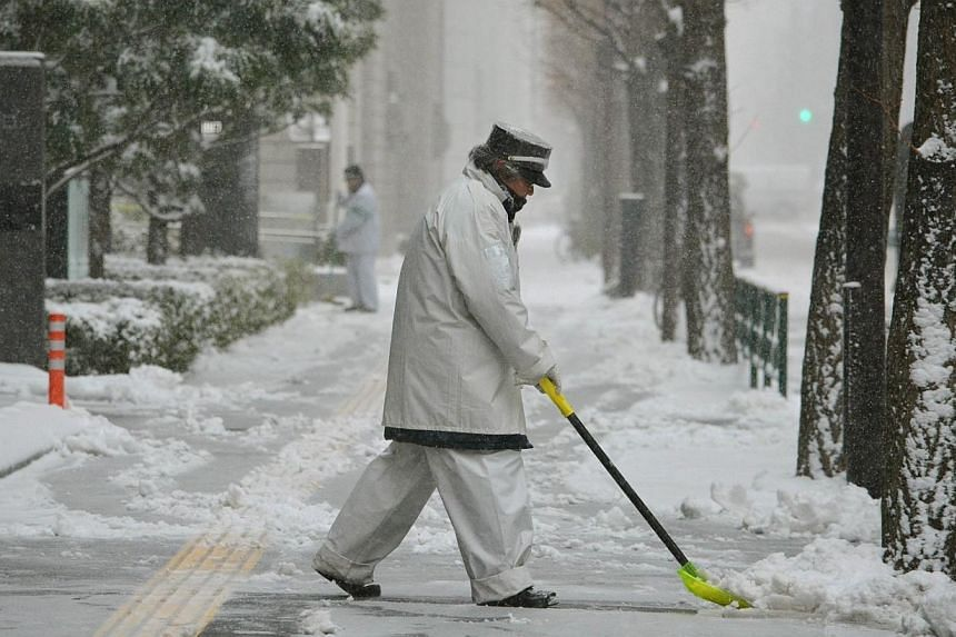 A worker removes snow from a sidewalk in Tokyo on Feb 8, 2014.Heavy snow struck Tokyo and other areas across Japan, grounding nearly 300 flights and suspending some train services as the weather agency issued a severe storm warning for the capi