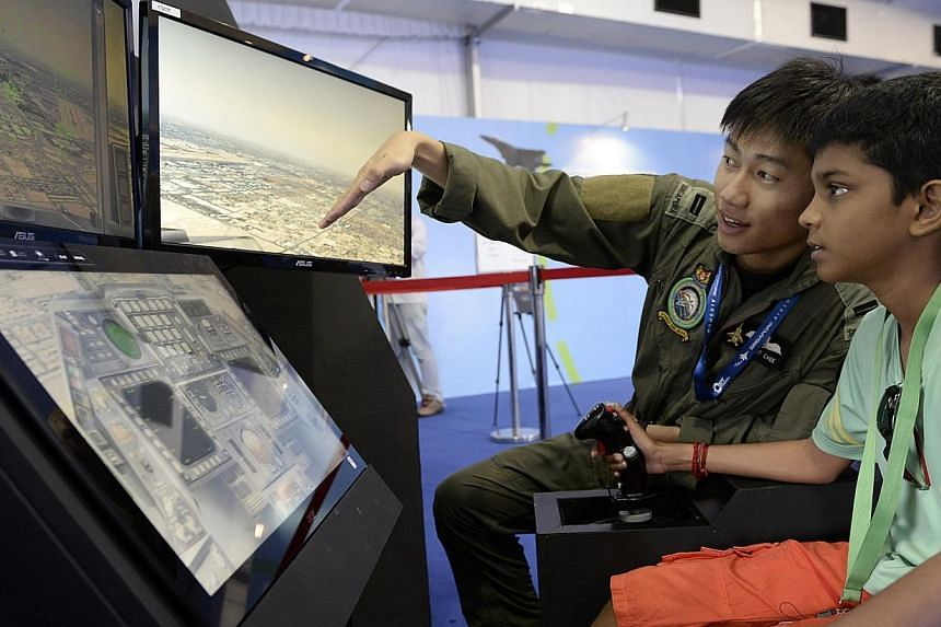 Weapons system officer Lieutenant Brant Chee, 26, leads 11-year-old Gajendran Vijayendran through a F16 flight simulator at the Republic of Singapore Air Force's (RSAF) 45th anniversary Family Day celebrationson Saturday, Feb 8, 2014. -- ST PHO