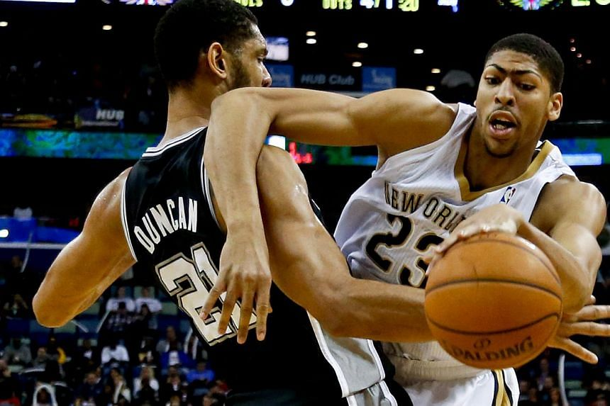 New Orleans Pelicans power forward Anthony Davis (23) collides with San Antonio Spurs power forward Tim Duncan (21) during the third quarter of a game at the New Orleans Arena onJan 13, 2014.Davis was named on Friday by NBA commissioner A