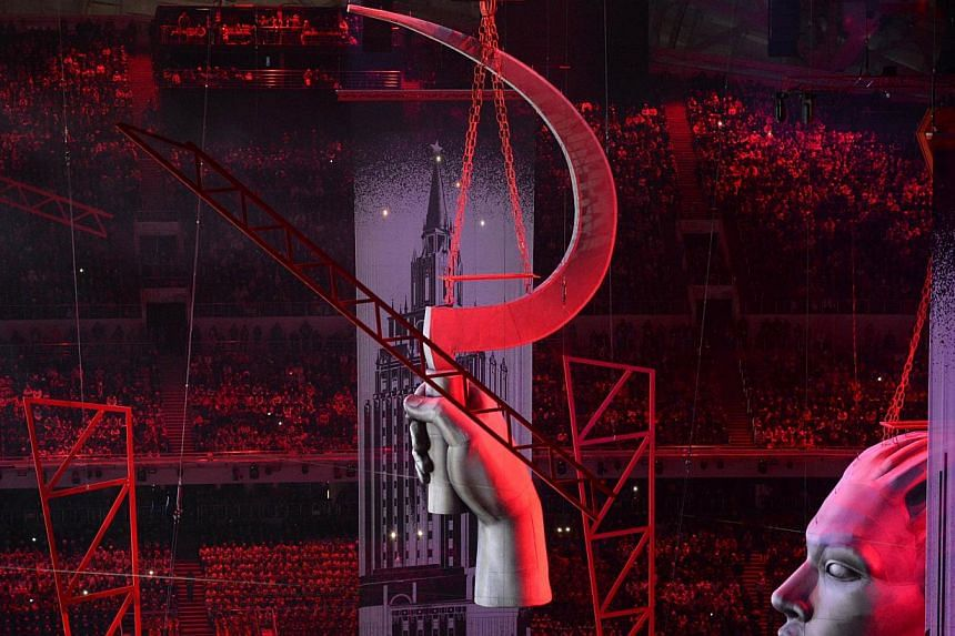 A sculpture portraying a sickle floats above a street scene during the Opening Ceremony of the Sochi Winter Olympics. -- PHOTO: AFP