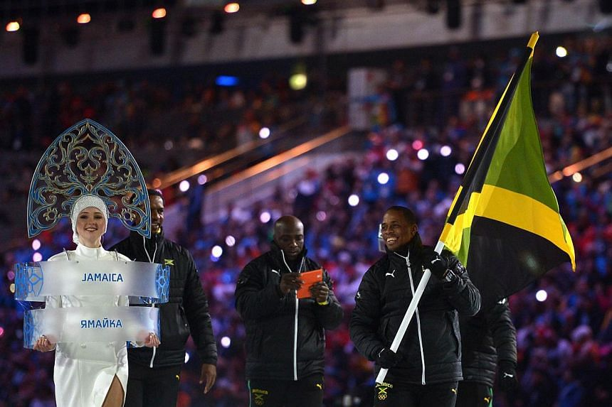 Jamaica's flag bearer, bobsledder Marvin Dixon, leads his national delegation during the Opening Ceremony of the 2014 Sochi Winter Olympics at the Fisht Olympic Stadium. -- PHOTO: AFP