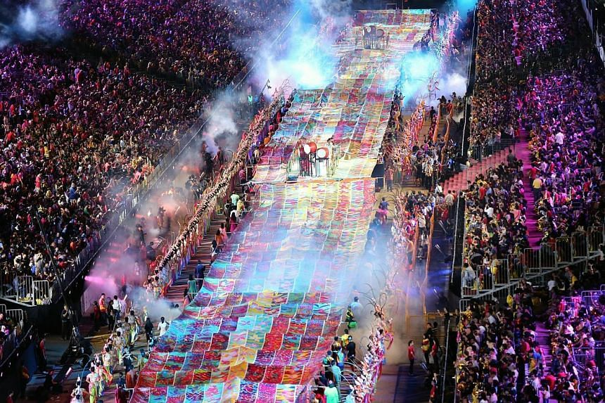 Singapore's largest batik painting being carried through the F1 Pit Building by volunteers at the Chingay parade last night. The 360m-long banner was painted by 40,000 new immigrants and locally born Singaporeans. -- PHOTO: LIANHE ZAOBAO