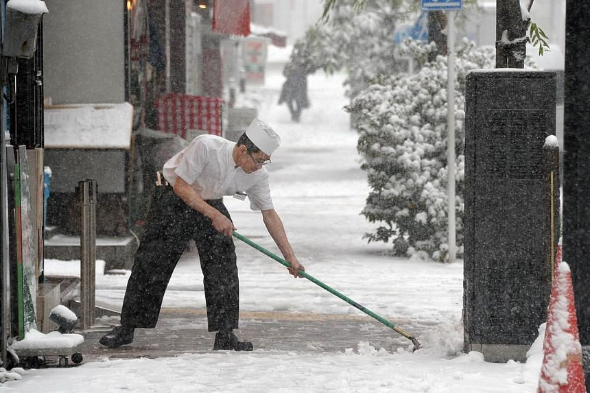 A cook tries to remove snow from the sidewalk in front of his restaurant in downtown Tokyo on Feb 8, 2014. Heavy snow struck Tokyo and other areas across Japan, grounding nearly 300 flights and suspending some train services as the weather agency iss