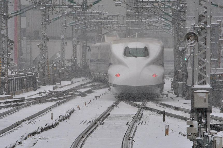 A bullet train leaves JR Tokyo Station in the snow on Feb 8, 2014. Wide areas of Japan were hit by snowfall with central Tokyo covered with snow in the morning. -- PHOTO: AFP