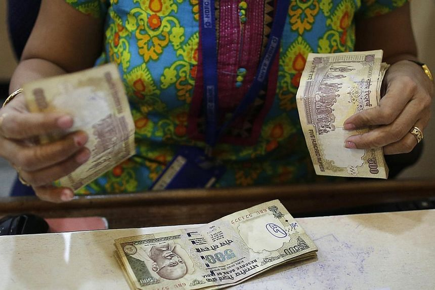 A cashier counts Indian rupee currency notes inside a bank in Mumbai. --PHOTO: REUTERS
