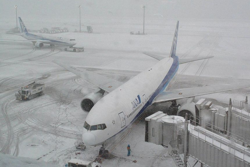 All Nippon Airways jetlinersare parked at Tokyo's Haneda airport covered in snow on Saturday, Feb 8, 2014. Heavy snow and severe weather struck Tokyo and other areas across Japan on Saturday, leaving three dead, reports said. -- PHOTO: AFP