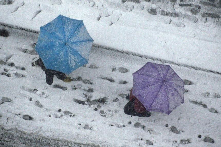 People holding umbrellas as they walk on the street covered with snow in Tokyo on Feb 8, 2014. -- PHOTO: AFP