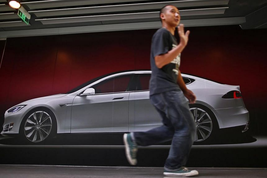 A man walking past a billboard-sized photo of the Tesla Model S car, outside the boarded-up Tesla's first China flagship showroom at an office-shopping complex in Beijing in this August 23, 2013 file photo. In an unusual blog post, the firm detailed