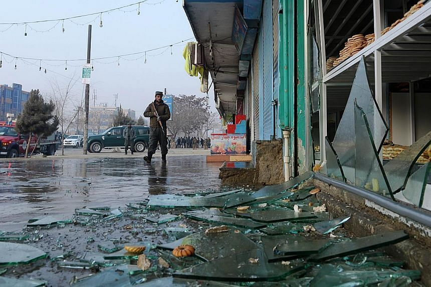 An Afghan policeman looks on amid broken glass and debris at the site of a suicide attack in Kabul on January 26, 2014. A Taleban suicide bomber killed at least four people in Kabul on January 26 when he targeted a Ministry of Defence bus, officials