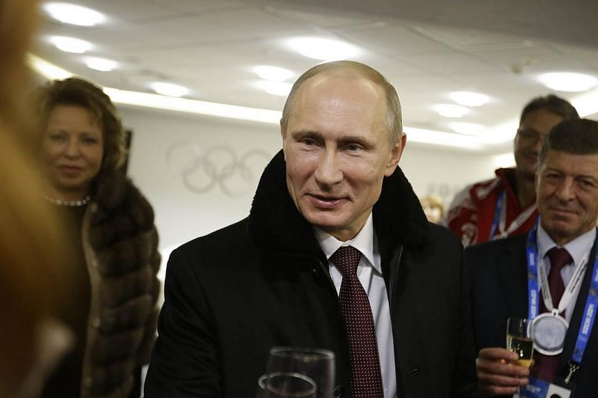 Russian President Vladimir Putin (centre) toasts guests in the presidential lounge as Deputy Prime Minister Dmitry Kozak (right) looks on following the opening ceremony of the 2014 Winter Olympics on Friday, Feb 7, 2014, in Sochi. Mr Putin will visit