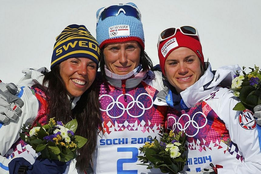 (From left) Sweden's Charlotte Kalle and Norway's Marit Bjoergen and Heidi Weng celebrate during the flower ceremony after the women's cross-country skiathlon event at the 2014 Sochi Winter Olympics.Bjoergen earned her fourth Olympic gold medal