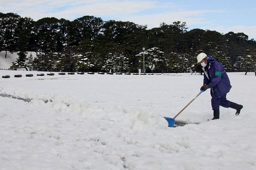 A man shovels snow to make a path at a park in Tokyo on Feb 9, 2014, one day after a heavy snowfall hit the capital. -- PHOTO: AFP