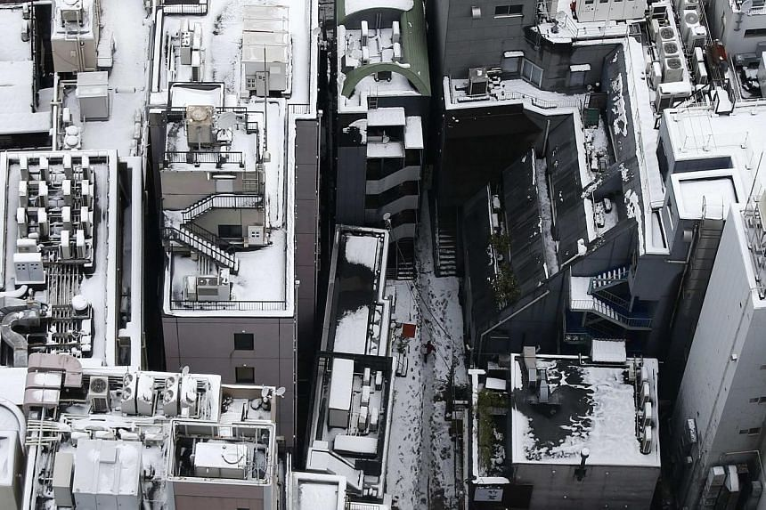 A man walks between office buildings that are covered with snow in Tokyo on Feb 9, 2014. -- PHOTO: REUTERS