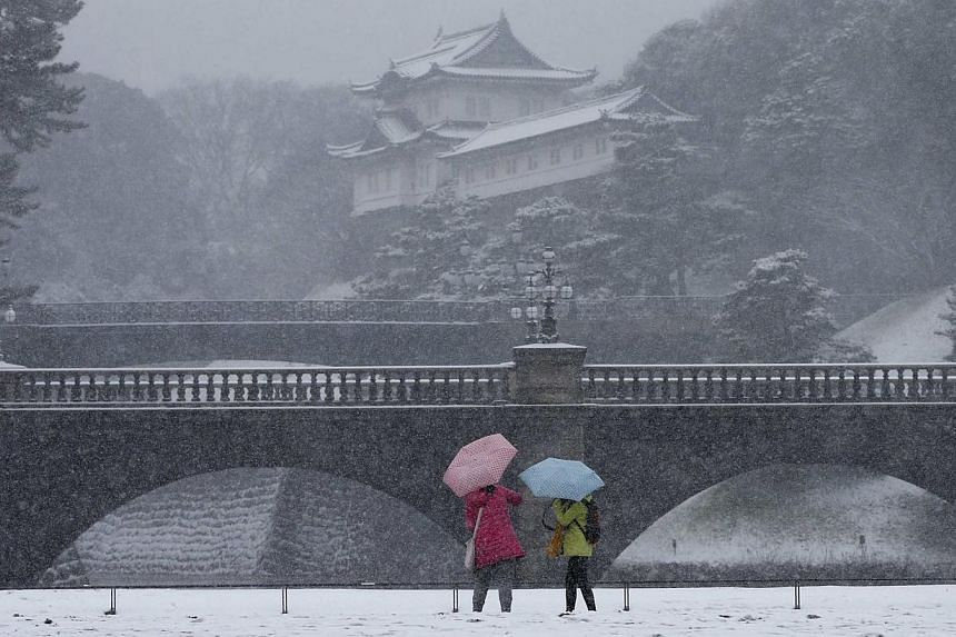 Visitors take photos at the Imperial Palace as snow falls in Tokyo on Feb 8, 2014. -- PHOTO: REUTERS