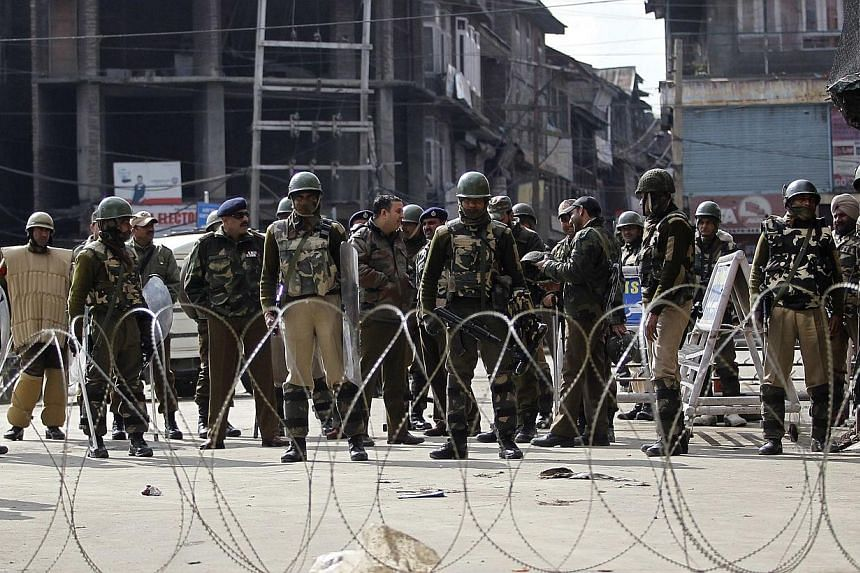 Indian security personnel stand guard behind concertina wire during strict restrictions in Srinagar on Feb 9, 2014.Most of Indian Kashmir was under curfew on Sunday to prevent protests marking the first anniversary of the hanging of a local sep