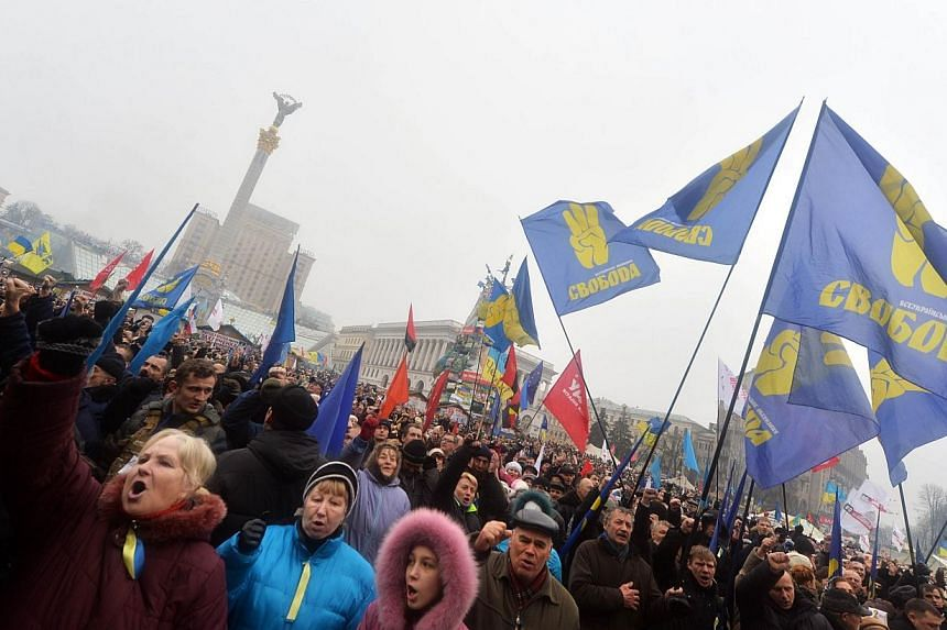 People hold up their fists and shout slogans during a mass opposition rally on Independence Square in Kiev on Feb 9, 2014. An estimated 70,000 pro-Western Ukrainians thronged the heart of Kiev on Sunday, vowing never to give up their drive to oust Pr