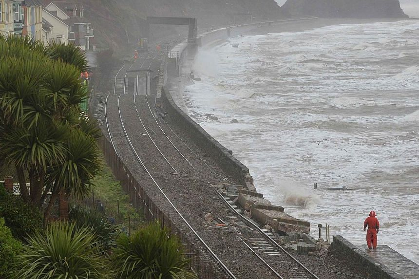 Rail emergency workers inspect damaged track along the seafront at Dawlish in south west England on Feb 6, 2014.Severe flooding and landslips have completely cut off rail routes to large parts of south-west of England as storms continue to batt