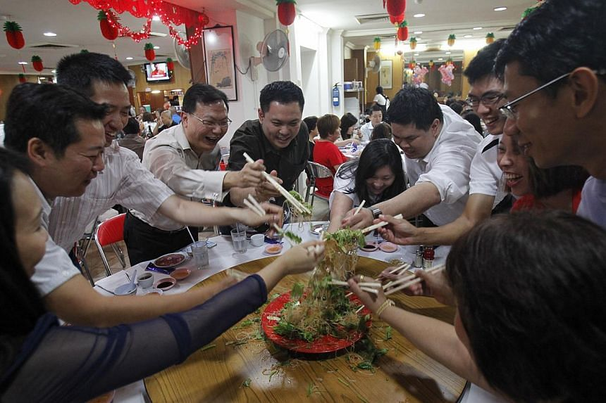 TeoChew Nang Facebook group members tossing yusheng at Lee Kui (Ah Hoi) Restaurant last Friday. The 12 spent the evening conversing in Teochew over a sumptuous meal with dishes such as Teochew-style braised duck and pomfret.